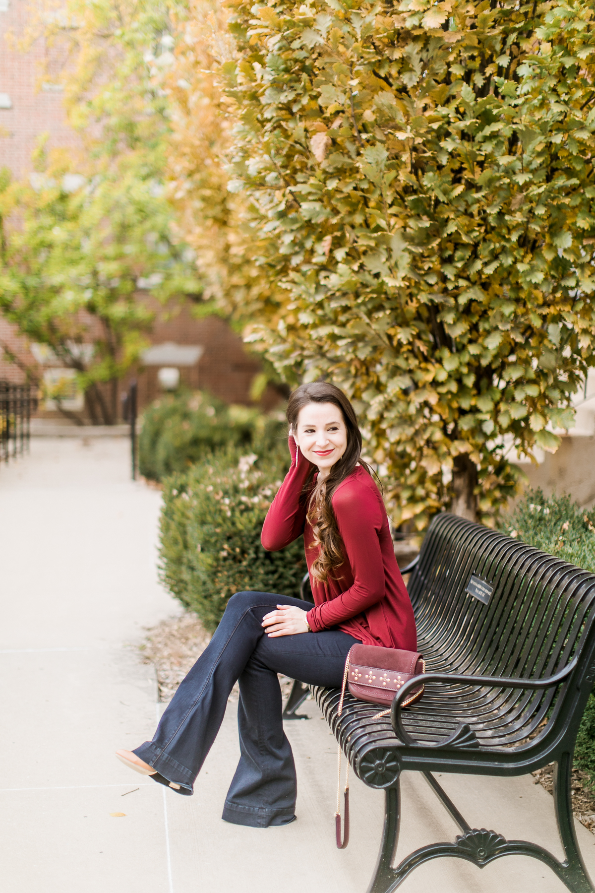 Long sleeve burgundy surplice top with dark wash flare jeans | Casual Thanksgiving outfit idea | What to Wear Out on Thanksgiving Eve by fashion blogger Stephanie Ziajka from Diary of a Debutante